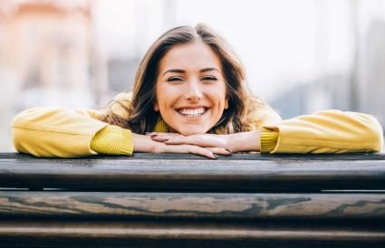 Smiling young woman sitting on a bench