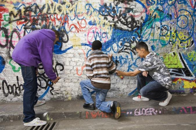 Teens spraying graffiti on wall
