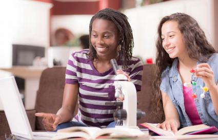 Teenage girls studying science at home