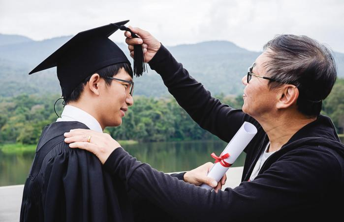 Father Adjusting Mortarboard Of Son
