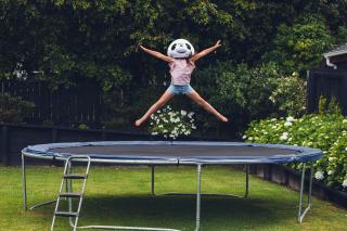 Girl wearing panda mask on trampoline