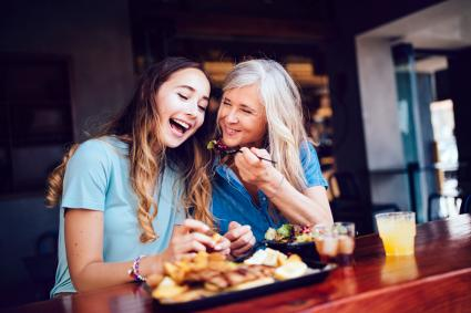 Smiling mother and teen daughter sharing lunch at a modern restaurant in the city
