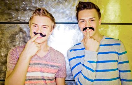 Two young men wearing fake mustaches