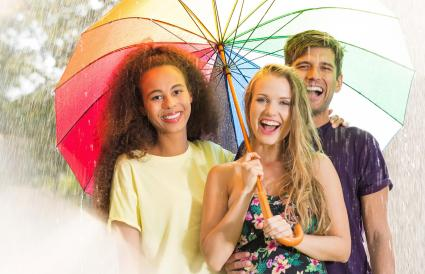 Happy friends under umbrella
