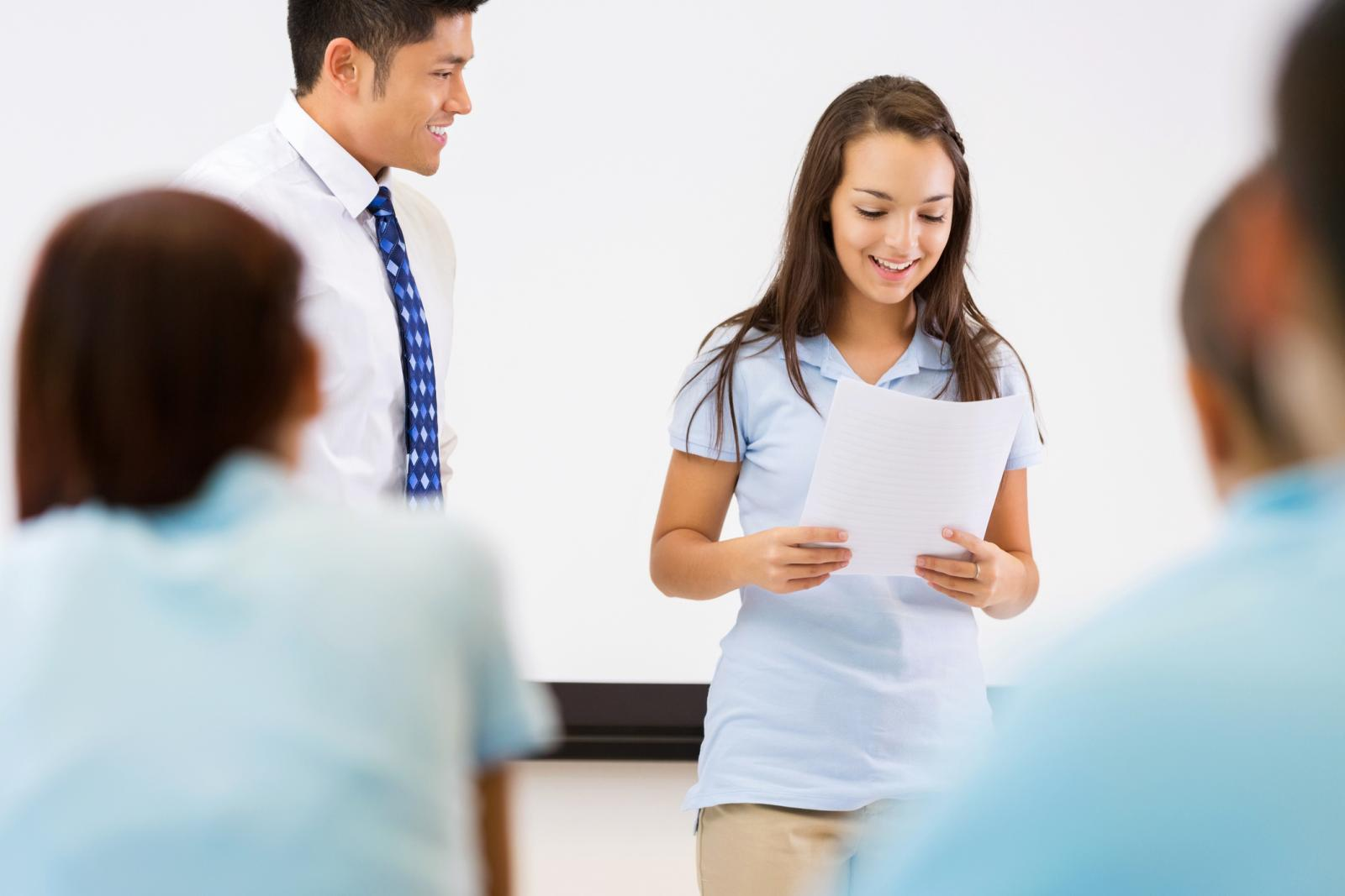 Girl smiling and speaking in front of class