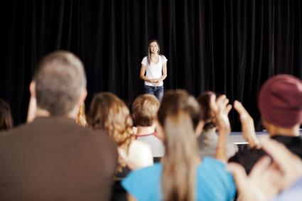 Audience clapping for a teenage girl on stage