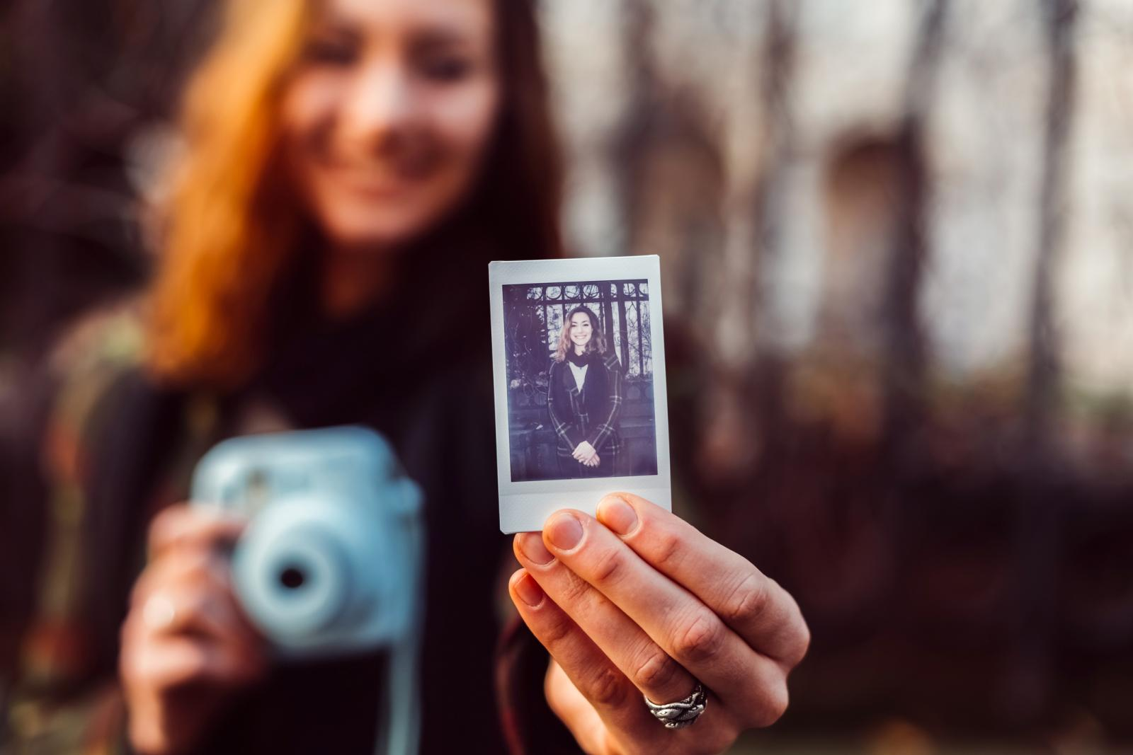 Smiling girl making instant photos with polaroid camera