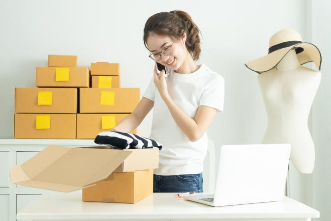 Teen girl packing boxes with clothes