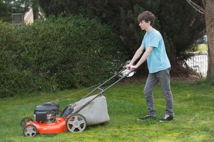 Teen boy mowing lawn