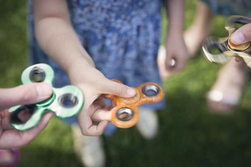 Hands holding fidget spinners