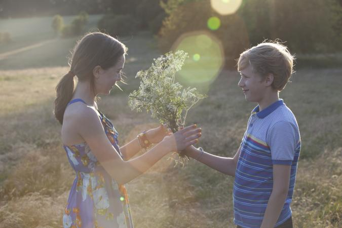 Young teen boy giving a girl flowers