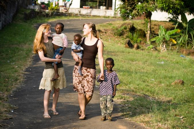 Two young missionaries with African children