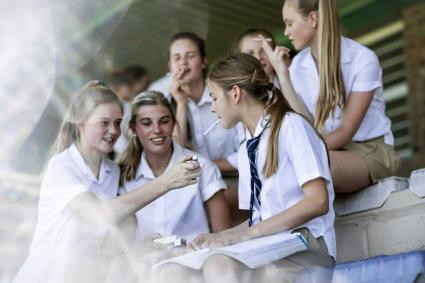 Female high school students smoking a cigarette