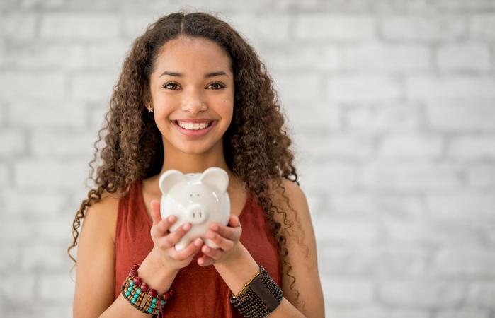 Teenage girl holding a piggy bank