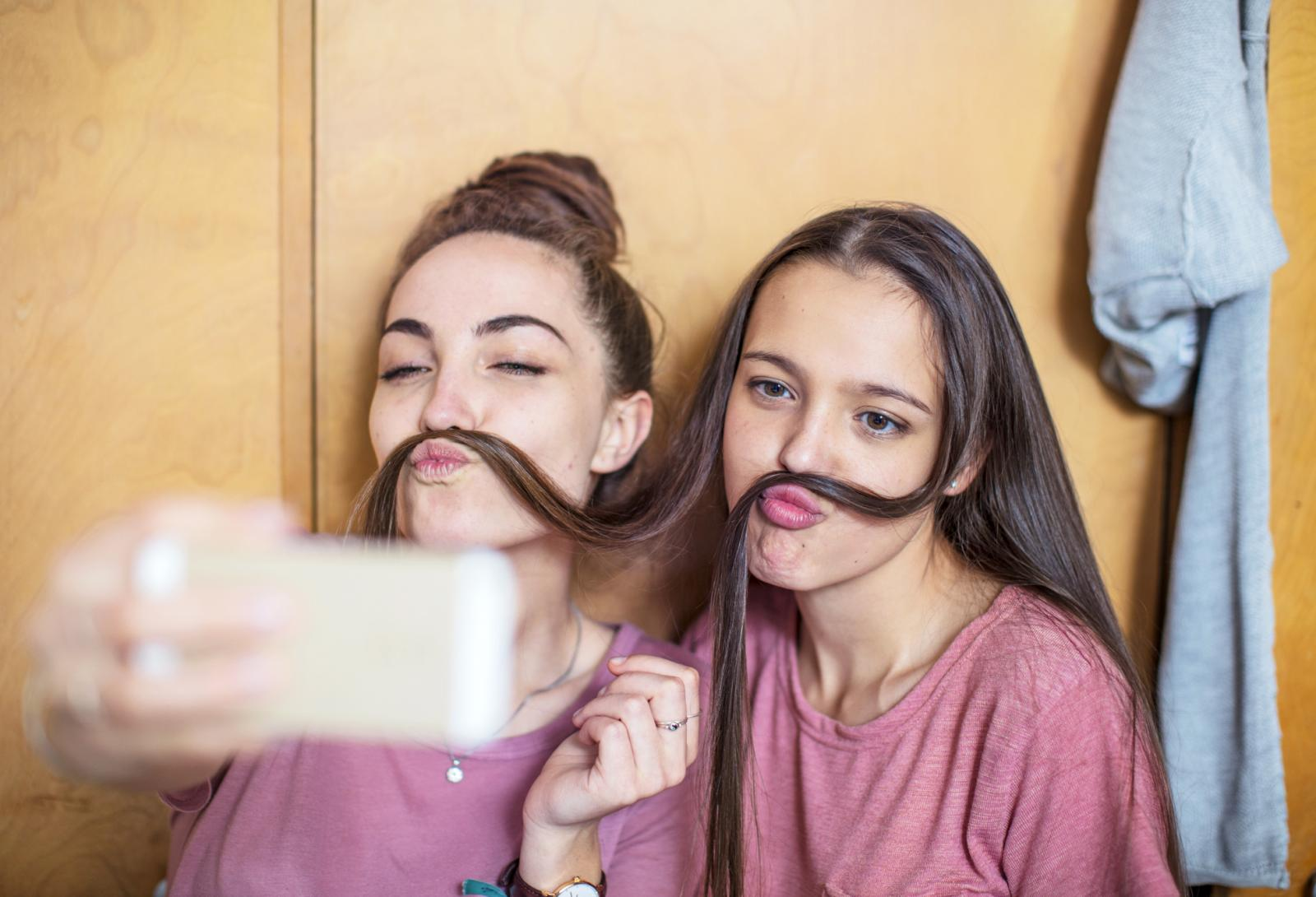 Playful happy teenage girls taking a selfie