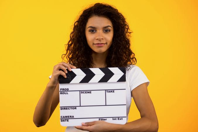 Young woman holding film clapper board