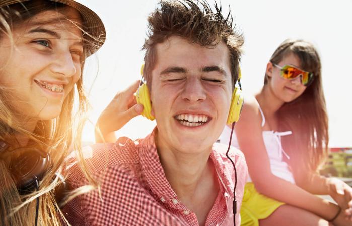 happy teenage friends with headphones outdoors