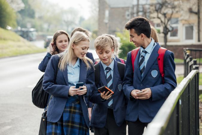 Teens wearing school uniforms laughing while walking to class