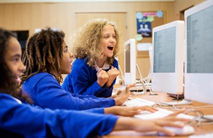 Teen girls at boarding school working on computers