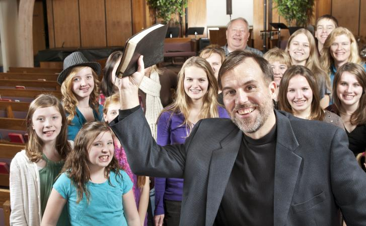 Pastor holding Bible with youth group