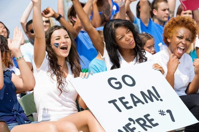 Excited high school sports fans cheering and holding sign
