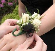 Guy putting a wrist corsage on his prom date