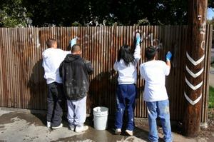 Teen youth club removing graffiti from a fence