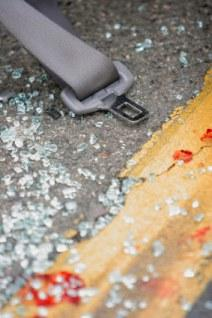 Seat belt laying on the road with broken glass