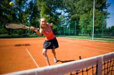 Teen girl getting exercise playing tennis