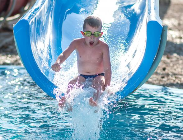 Boy splashing down on blue waterslide