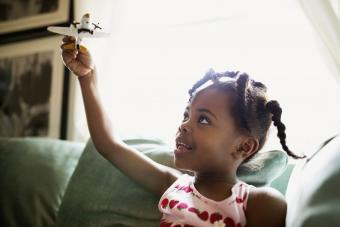 Girl flying toy airplane