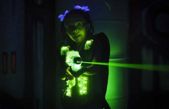 A little girl playing laser tag