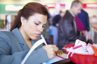 Woman at the airpot writing on a luggage tag