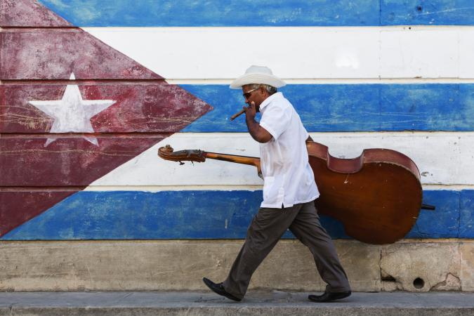 musician in front of Cuban flag mural
