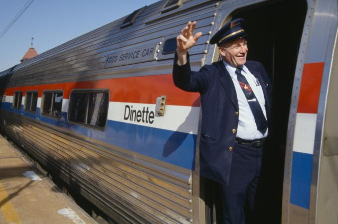 Amtrak conductor waving from inside train