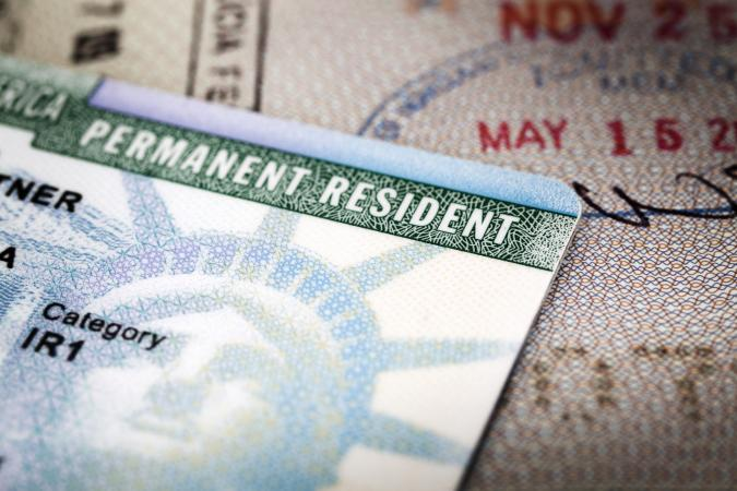 Green card lying on open passport