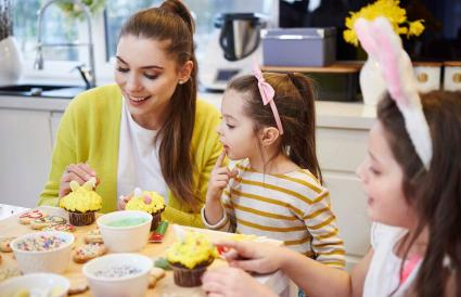 Mother with daughters decorating cupcakes