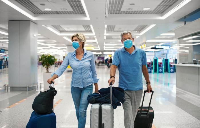 couple at an airport with facemasks