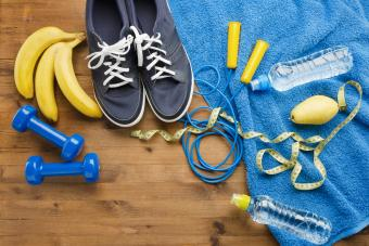 Fitness concept with sneakers dumbbells skipping rope measure tape towel bottle of water pear and bananas