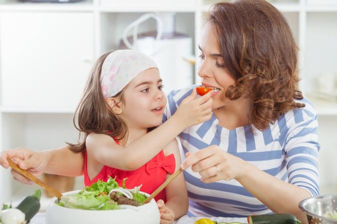 Kid and mom eating veggies together