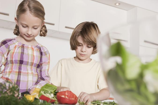 Two kids cooking with veggies together