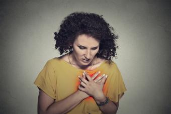Woman clutching chest over heart