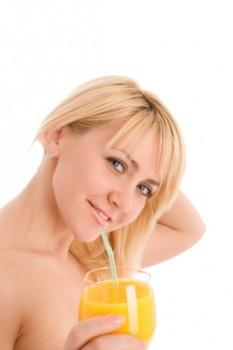 Woman drinking orange juice with straw