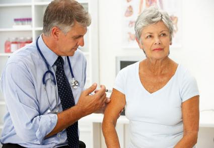 Doctor injecting senior female patient