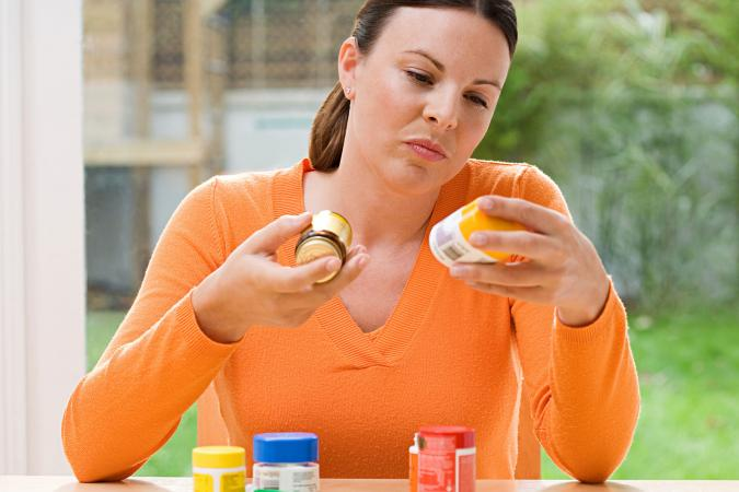Woman choosing between vitamin supplements