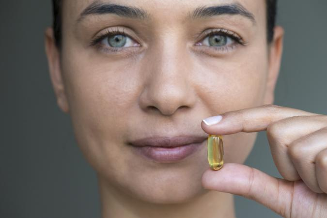 Woman Holding Vitamin E Capsule