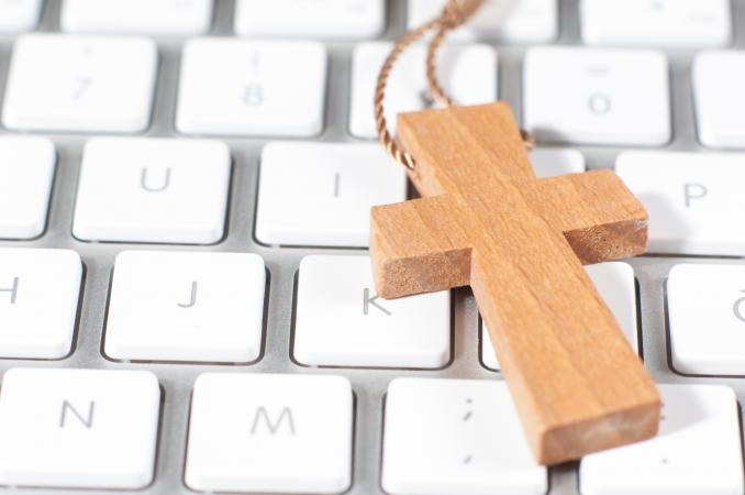 Christian cross necklace on computer keyboard