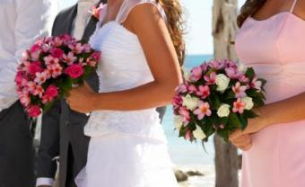 Bride wearing white and bridesmaid wearing pink
