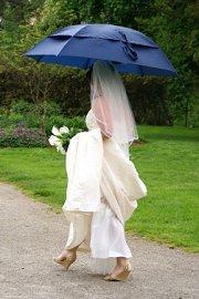 Bride using an umbrella at her outdoor wedding