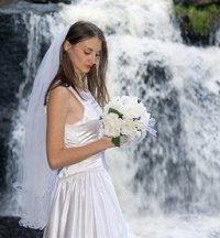 Bride holding her bouquet near a waterfall